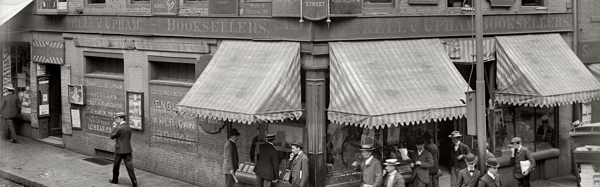 בוסטון סביב 1900. חנות הספרים הפינתית בבניין הלבנים הותיק בעיר. באדיבות: דטרויט פבלישינג קומפני גלויה של דטרויט פבלישינג קומפני