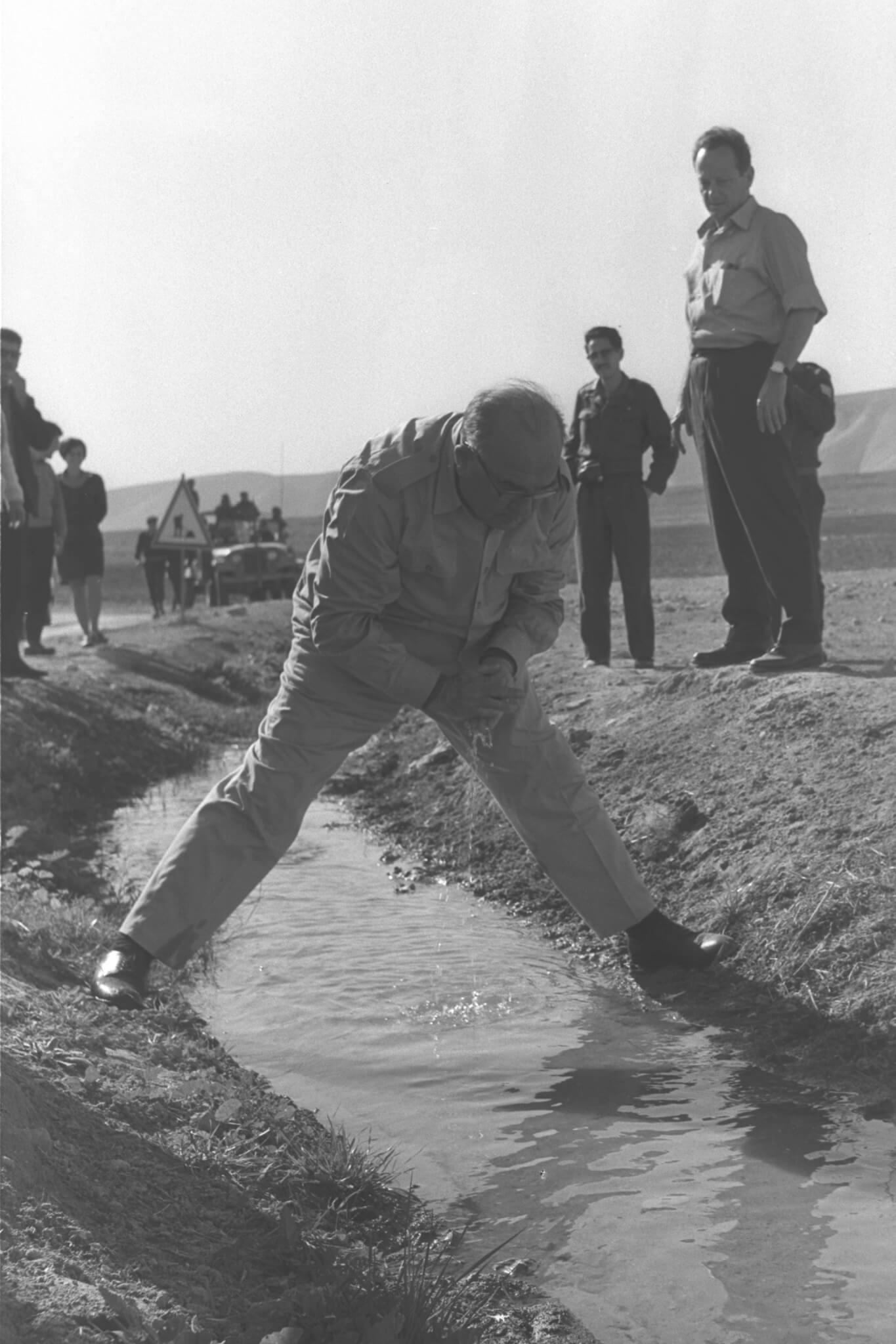 """נטוע בשתי הגדות. ראש הממשלה לוי אשכול שותה ממימי מעיין פצאל בעת סיור בבקעת הירדן, דצמבר 1967. מאחוריו השר יגאל אלון. צילום משה מילנר, לע""""מ"""