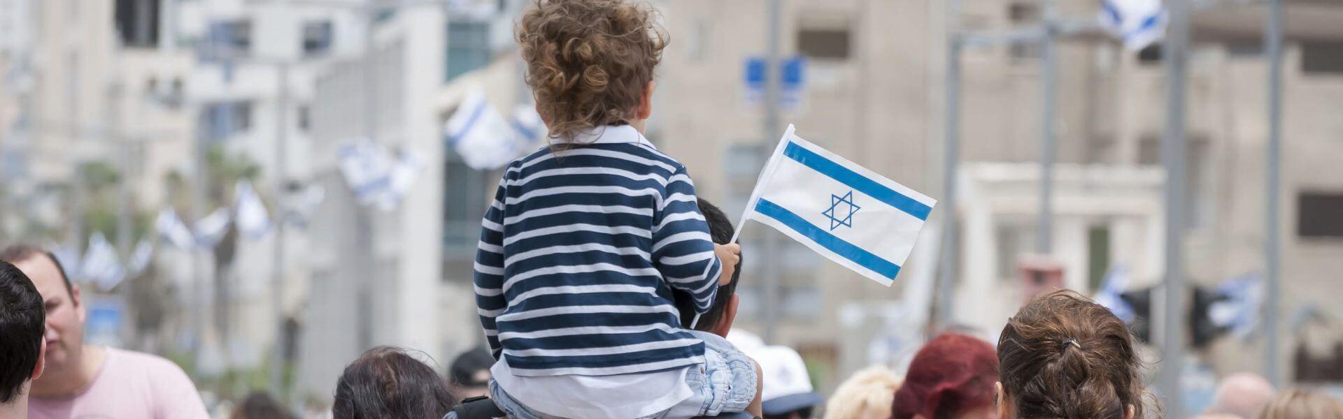 ילד יושב על כתפי אביו ואוחז בדגל ישראל. תמונה: Bigstock