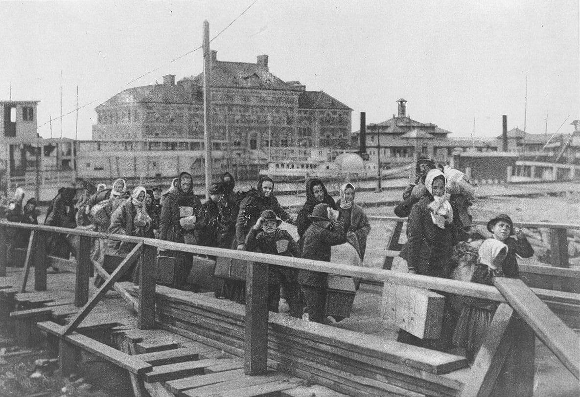 """Emigrants coming up the board-walk from the barge, which has taken them off the steamship company's docks, and transported them to Ellis Island. The big building in the background is the new hospital just opened. The ferry-boat seen in the middle of the picture, runs from New York to Ellis Island."" [Original text from Library of Congress ""About This Item"" page.]. Photo: Wikimedia Commons"