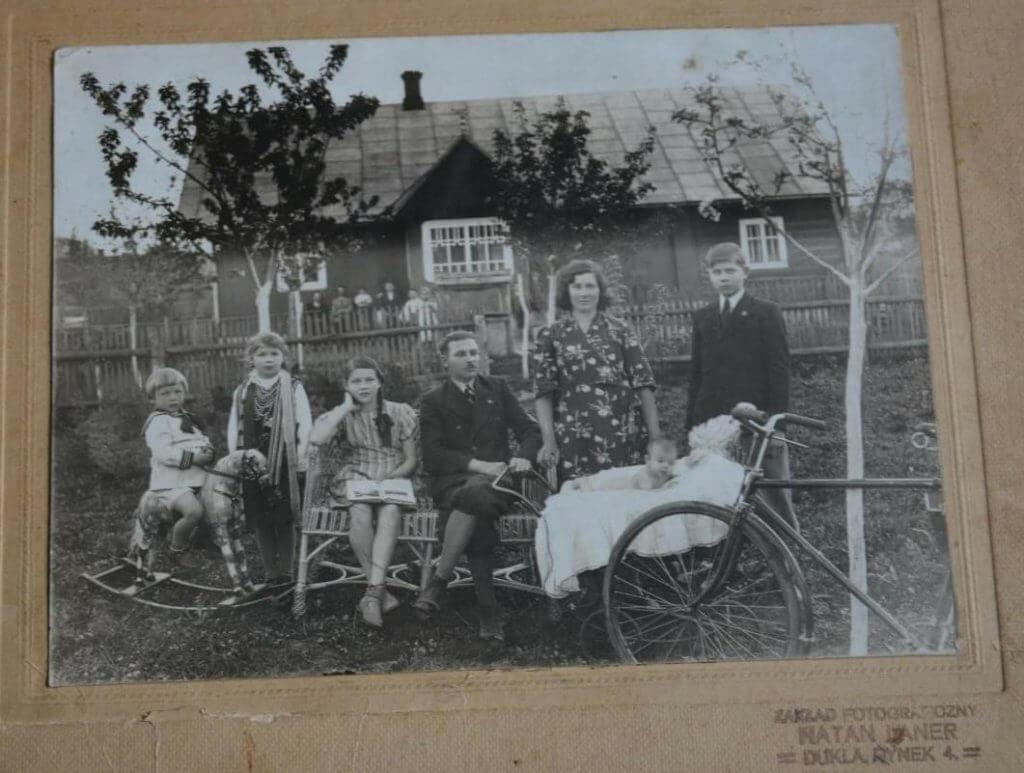פרנק ולצר ובני משפחתו ליד ביתם בצגורבה שבו הסתירו את האחים גוזיק, בצילום מלפני המלחמה.