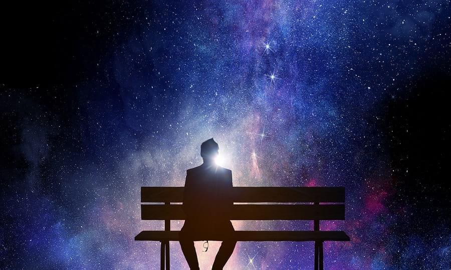 צללית איש יושב על ספסל על רקע שמי הלילה
