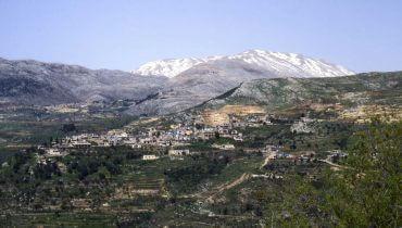 הכפר עין קיניא על רקע הר החרמון המושלג