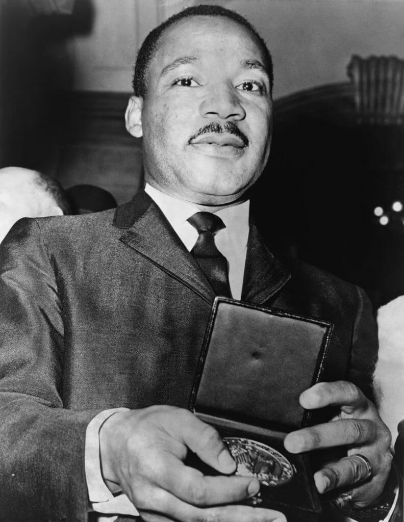 השוויון כדרישה דתית מובהקת. הכומר מרטין לותר קינג (ג'וניור), בעת קבלת מדליה ב-1964. צילום: פיל סטנציולה, NYWTS, מאוסף ספריית הקונגרס